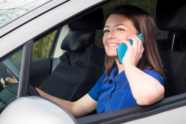Piękna dziewczyna, młoda kobieta jedzie samochodem, uśmiecha się i rozmawia przez telefon komórkowy. korzystanie ze smartfona podczas jazdy samochodem, za kierownicą. niebezpieczna sytuacja, nie zwracanie uwagi na drodze