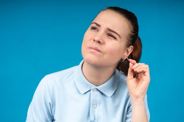 Piękna dziewczyna, młoda kobieta z swędzącymi uszami, czyszczenie usuwa woskowinę z brudnego słuchu
