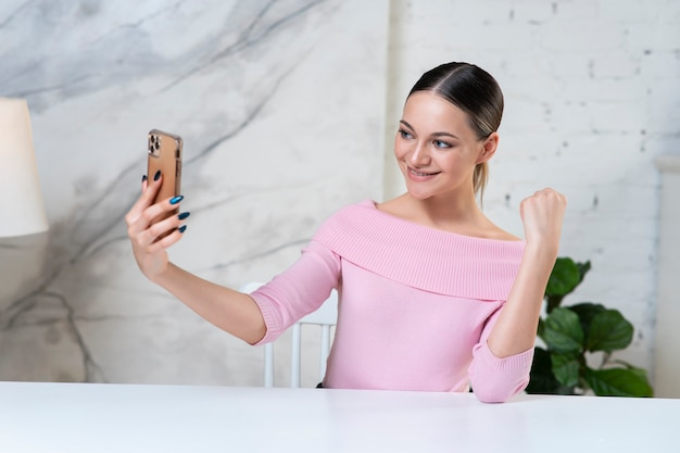 Piękna dziewczyna, młoda szczęśliwa blogerka szuka, rozmawia w aparacie, nadaje online na vlog