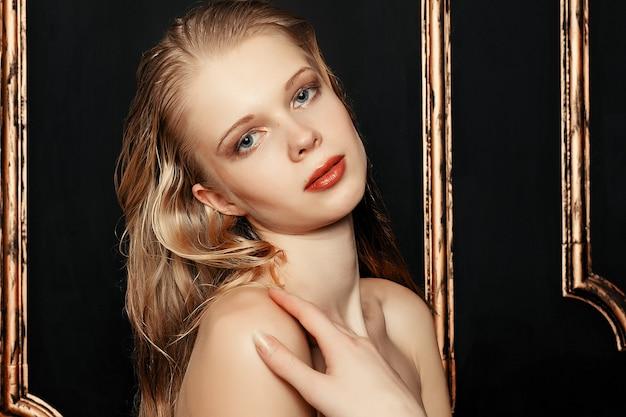 Piękna dziewczyna moda model naturalny makijaż mokre włosy na czarnym tle złota w ciepłych kolorach. portret młodej kobiety z makijażem mody