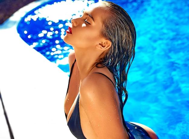 Piękna dziewczyna model o ciemnych włosach w czarnych strojach kąpielowych