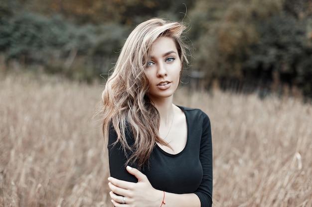Piękna dziewczyna model w czarnej koszulce pozowanie w polu kukurydzy