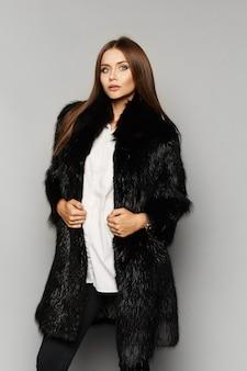 Piękna dziewczyna modelka z idealnym makijażem w luksusowe futro, na białym tle na tle.
