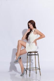 Piękna dziewczyna na białym tle na różowym tle. stojąc, patrząc w kamerę. biała sukienka i buty. piękna fryzura i makijaż. brunetka dziewczyna z długie czarne proste włosy latające. wspaniałe włosy.