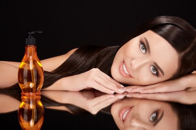 Piękna dziewczyna na czarnym szkle z olejkiem do włosów