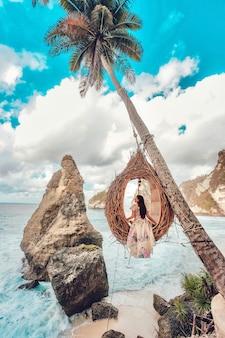 Piękna dziewczyna na huśtawkowych kokosowych palmach na plaży przy daimond plażą, nusa penida wyspa bali, indonezja