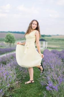 Piękna dziewczyna na lawendowym polu. piękna długowłosa kobieta w lekkiej pastelowej sukience pozowanie do kamery z uśmiechem w lawendowym polu na zachód słońca. nieostrość