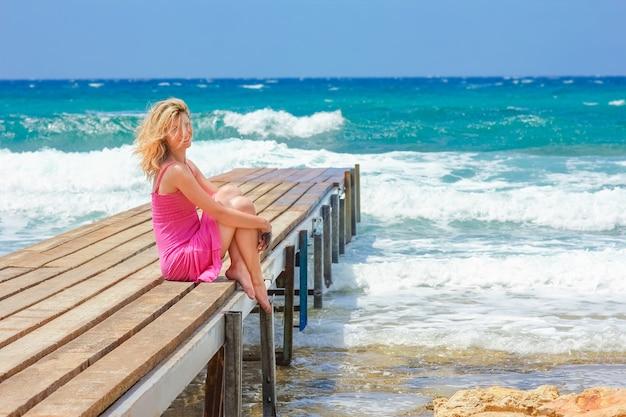 Piękna dziewczyna na molo nad brzegiem morza