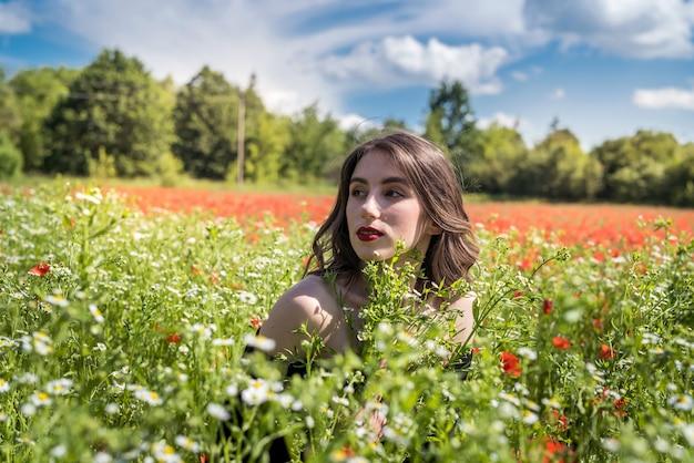 Piękna dziewczyna na polu kwiatów, słoneczny dzień