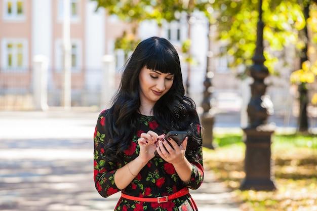 Piękna dziewczyna na spacerze na tle architektury z gadżetem w dłoniach. nawigacja i komunikacja