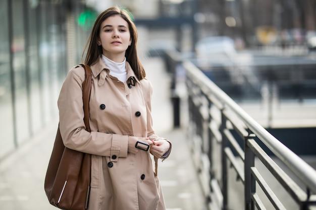Piękna dziewczyna na ulicy w płaszczu kawowym i brązowej skórzanej torbie