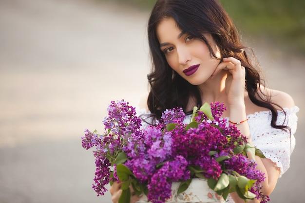 Piękna dziewczyna na zewnątrz. ładna młoda kobieta z bukietem bzu. dama z kwiatami z bliska