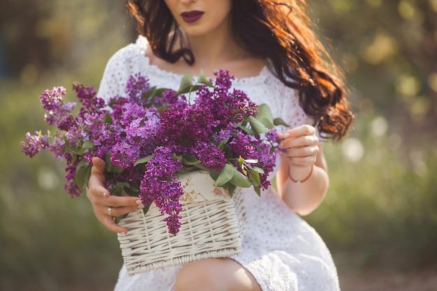 Piękna dziewczyna na zewnątrz. ładna młoda kobieta z bukietem bzu nie do poznania dama z kwiatami zamyka up