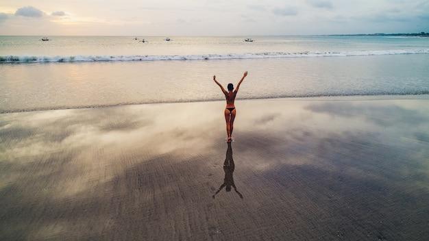 Piękna dziewczyna na zmierzchu tle na piaskowatej plaży