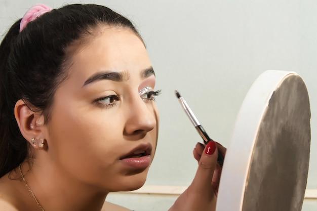 Piękna dziewczyna nakłada brokatowy makijaż na powieki w swojej sypialni