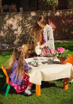 Piękna dziewczyna nalewa herbatę swojej siostrze na zabawkowej imprezie herbacianej