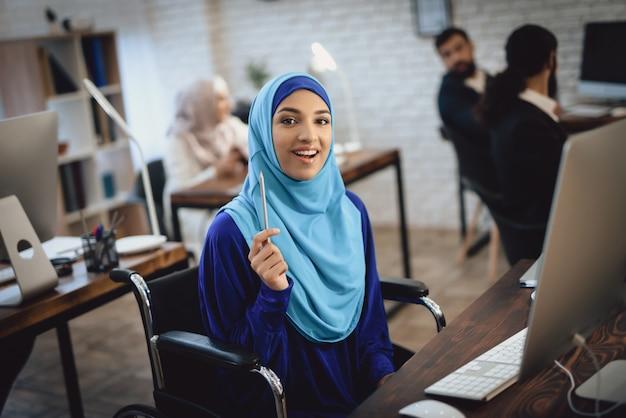 Piękna dziewczyna niepełnosprawnych uśmiecha się działa na komputerze.