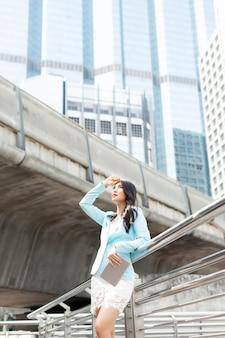 Piękna dziewczyna nosi ubrania kobieta biznesu, trzymając komputer typu tablet inteligentny telefon na tle dzielnicy biznesowej miasta, koncepcja biznesowa