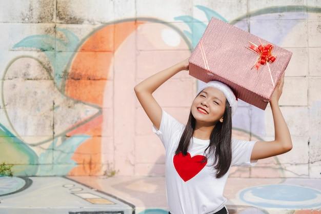 Piękna dziewczyna nosić boże narodzenie kapelusz trzymać obecny na kolorowym tle.