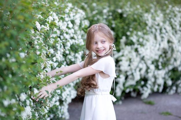 Piękna dziewczyna o blond długich włosach w białej delikatnej jedwabnej sukience, na tle kwitnących białych wiosennych kwiatów, trzyma kwiaty, figlarnie uśmiecha się i odwraca wzrok