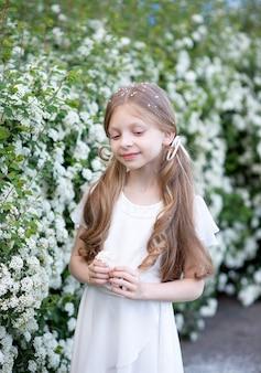 Piękna dziewczyna o blond długich włosach w białej delikatnej jedwabnej sukience