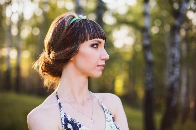 Piękna dziewczyna o ciemnych włosach i brązowych oczach z wieńcem na głowie w letniej sukience