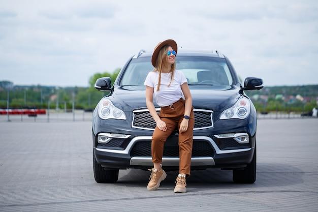 Piękna dziewczyna o europejskim wyglądzie w okularach i brązowym kapeluszu stoi obok czarnego samochodu. sesja zdjęciowa w pobliżu samochodu.