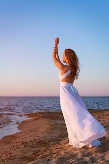 Piękna dziewczyna o kaukaskim wyglądzie stoi samotnie w długiej białej sukience nad brzegiem morza w...