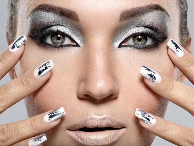 Piękna dziewczyna o srebrnym makijażu i metalowych paznokciach. portret kobiety moda.