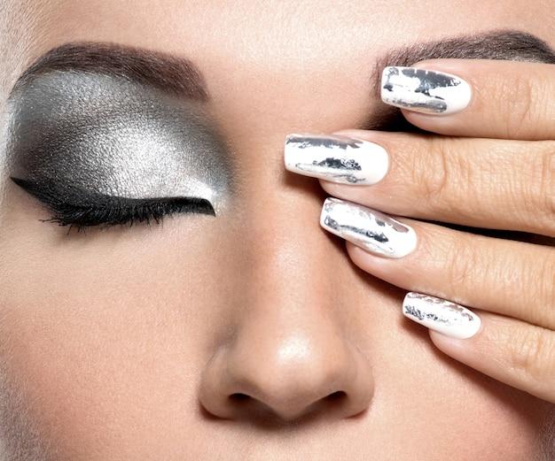 Piękna dziewczyna o srebrnym makijażu i metalowych paznokciach.