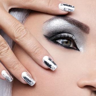 Piękna dziewczyna o srebrnym makijażu oczu i metalowych paznokciach.