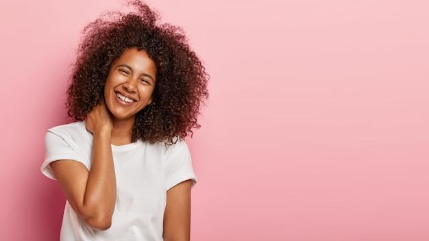 Piękna dziewczyna o zabawnym wyglądzie miło rozmawia, delikatnie dotyka szyi, śmieje się radośnie z zabawnego żartu, będąc w doskonałym nastroju ubrana w białą koszulkę stoi na różowej ścianie z miejscem na kopię