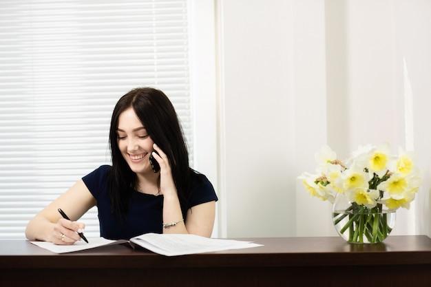 Piękna dziewczyna odbiera wezwanie w stomatologicznym biurze przy recepcyjnym biurkiem
