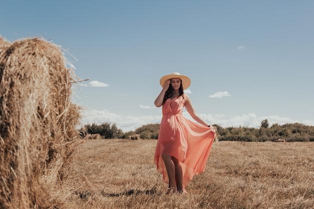 Piękna dziewczyna odpoczywa po pracy. dziewczyna na polu z sianem. kobieta w pobliżu snopu siana na polu. wiejskie życie. wakacje we wsi.
