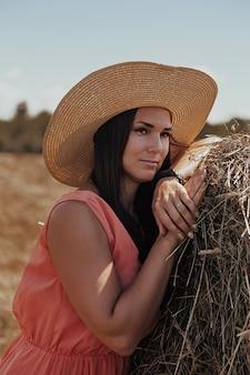 Piękna dziewczyna odpoczywa po pracy. dziewczyna na polu z sianem. kobieta w pobliżu snopu siana na polu. wiejskie życie.