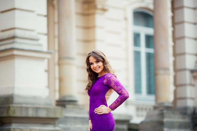 Piękna dziewczyna ono uśmiecha się w purpurowej błękit sukni