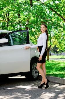 Piękna dziewczyna otwiera drzwi swojego samochodu i siada na siedzeniu kierowcy