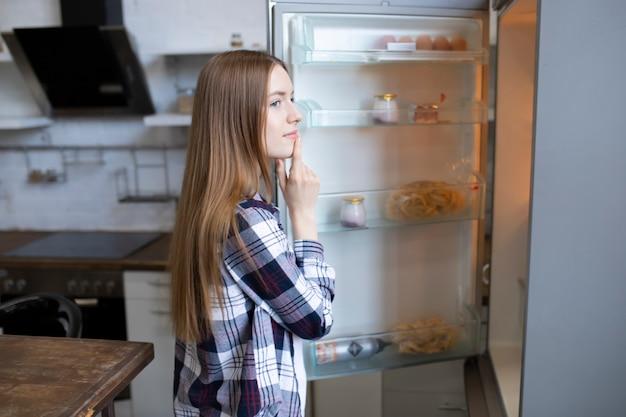 Piękna dziewczyna otwiera lodówkę i zastanawia się, co zjeść