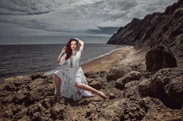 Piękna dziewczyna, panna młoda, w białej sukni, boso siedzi na kamieniach