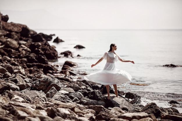 Piękna dziewczyna, panna młoda w białej sukni, stojąca boso na kamieniach