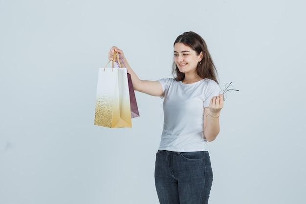 Piękna dziewczyna patrząc na torby na prezenty w t-shirt, dżinsy i szczęśliwy patrząc. przedni widok.