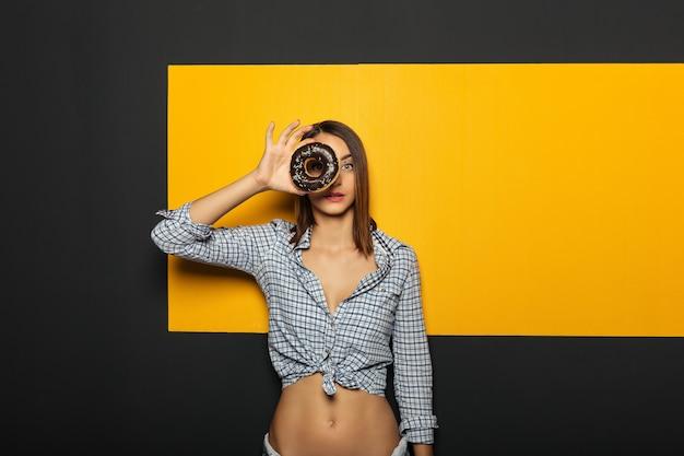 Piękna dziewczyna patrzeje ciekawy przez pączka kamera