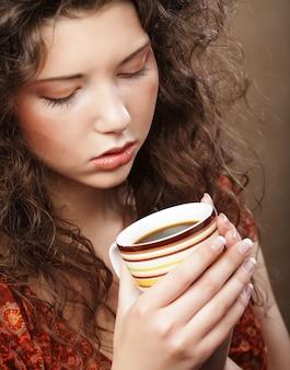 Piękna dziewczyna pije herbatę lub kawę.