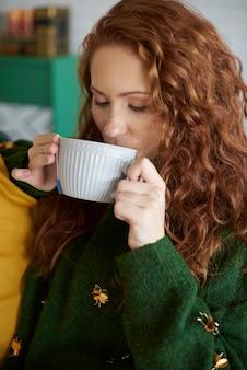 Piękna dziewczyna pije herbatę w jesienny poranek