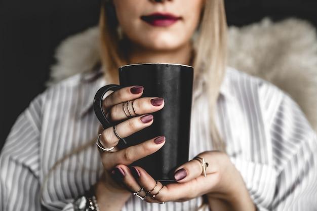 Piękna dziewczyna pije kawę z czarną filiżanką w koszuli, moda, jedzenie