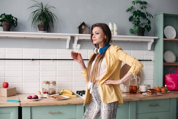Piękna dziewczyna pije sok w domu w ranku