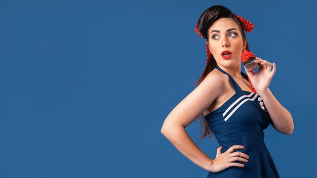 Piękna dziewczyna pinup pozowanie w niebieskim studio