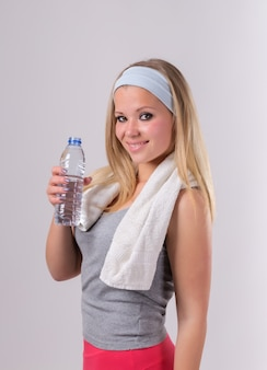 Piękna dziewczyna po sprawności fizycznej z bidonem. z ręcznikiem i uśmiechem.