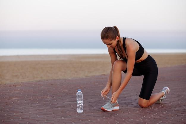 Piękna dziewczyna podczas biegania wiąże sznurówki w trampkach