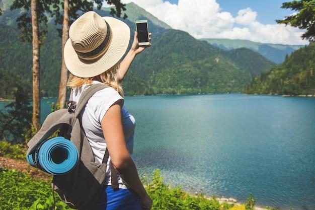 Piękna dziewczyna podróżnik w kapeluszu stoi na jeziorze i robi zdjęcia na tle gór